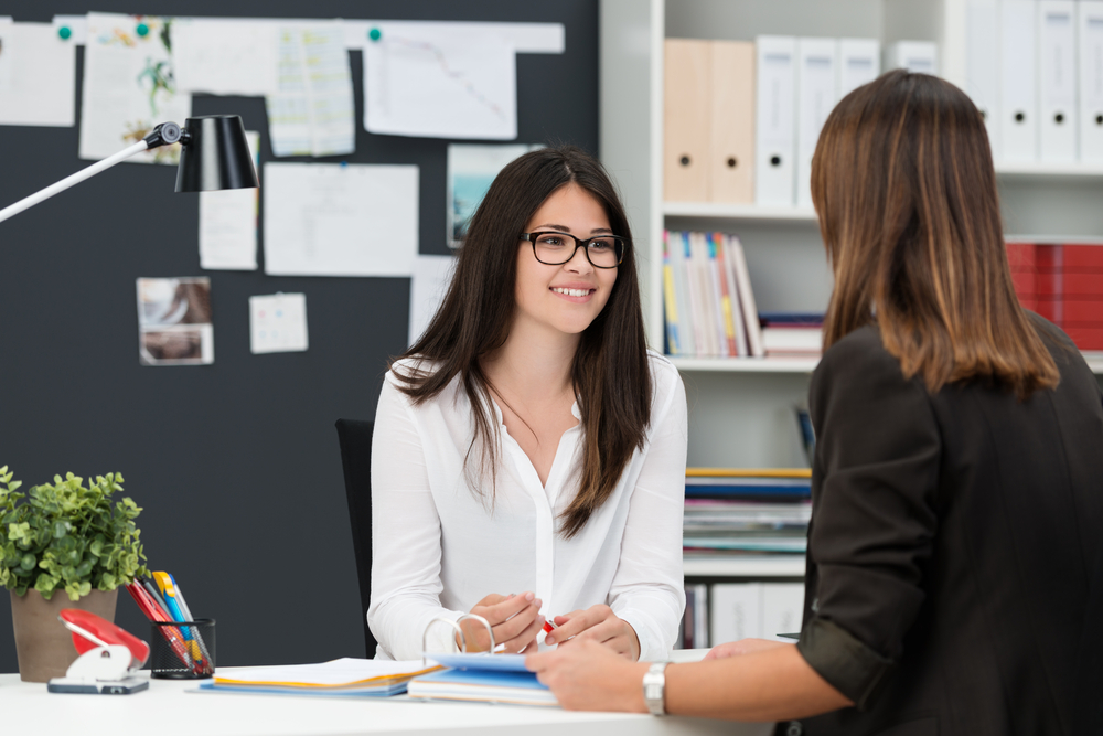 Two women sitting at a desk in an interview setting