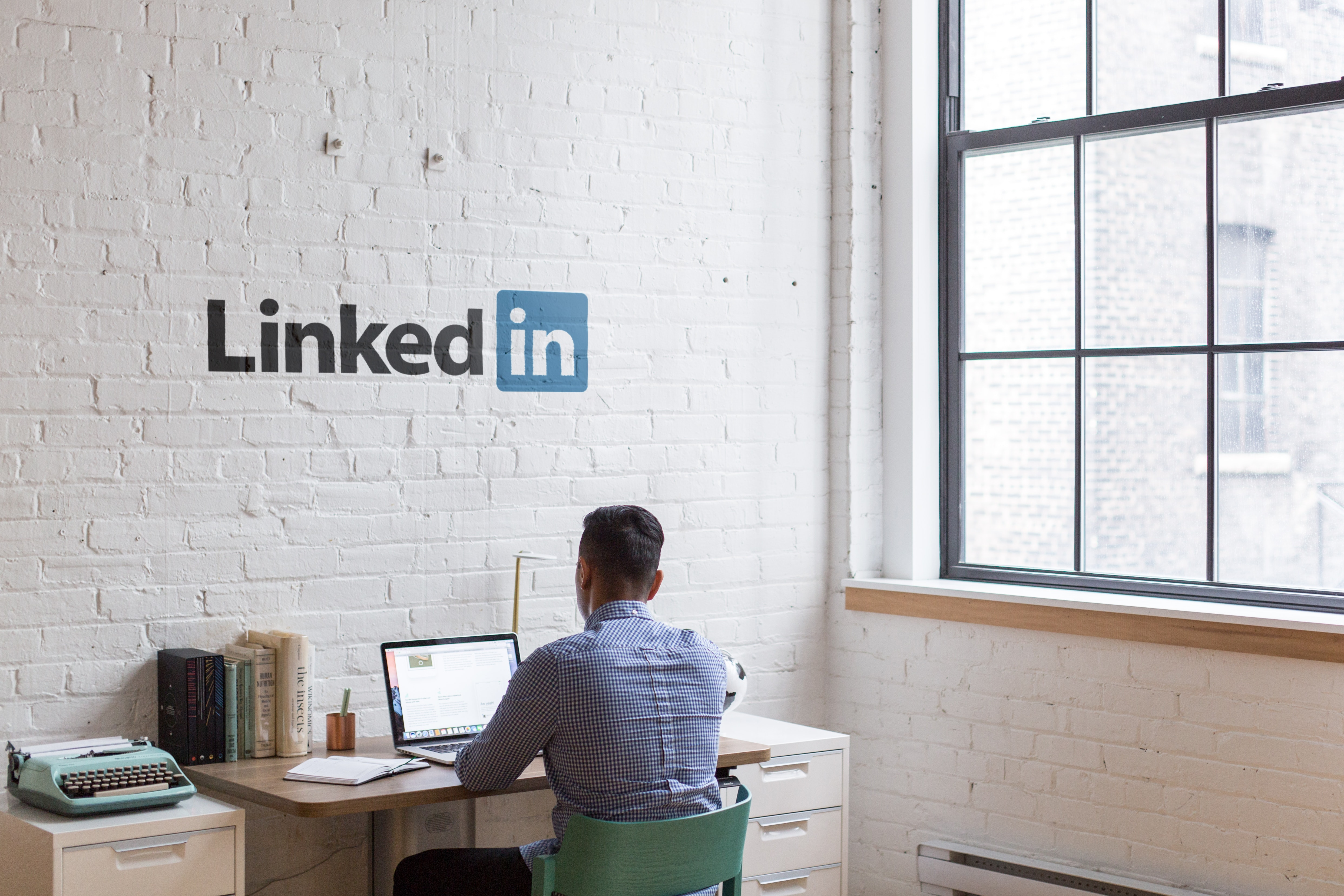man sitting at a desk facing a white wall that says LinkedIn